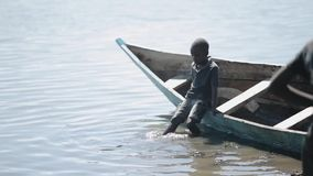 KENYA, KISUMU - MAY 20, 2017: Beautiful African boy is sitting in the boat on the shore of the lake and swinging his