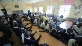 KENYA, KISUMU - MAY 23, 2017: Big group of african kids and teenagers sitting, caucasian volunteers help make bracelets. KENYA, KISUMU - MAY 23, 2017: Big group royalty free stock photos