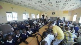 KENYA, KISUMU - MAY 23, 2017: Big group of african kids and teenagers sitting, caucasian volunteers help make bracelets. KENYA, KISUMU - MAY 23, 2017: Big group royalty free stock photo