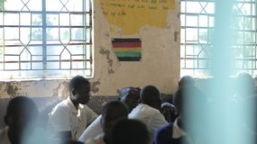 KENYA, KISUMU - MAY 23, 2017: Close-up fiew of three african boys in uniform sitting in classroom in school royalty free stock photography