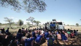 KENYA, KISUMU - MAY 20, 2017: Crowd of African children sitting on ground and listen Caucasian men and women.