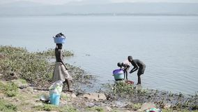 KENYA, KISUMU - MAY 20, 2017: Woman and her daughter wash dishes in lake, girl carry basin with clothes on head. stock footage