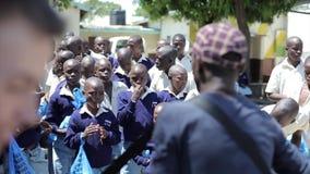 KENYA KISUMU, 15 05 2018 Ung man med gitarrallsång till gruppen av afrikanska barn i likformig Ungar near skolabyggnad stock video