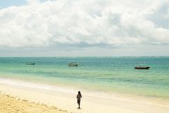 Kenyan beach. Boats and men on the beach Royalty Free Stock Photo