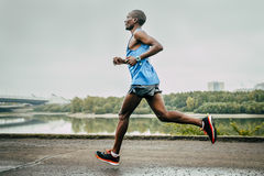 Kenyan John Kyui runs along the river Royalty Free Stock Photography