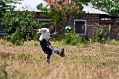 Kenyankerl, der Fußball spielt Stockfotos