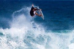 Keoni Jones que practica surf en la punta rocosa en Hawaii Imagen de archivo libre de regalías