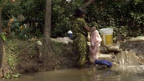 Kerala Backwaters. An Indian Woman Washes Her Clothes. stock footage