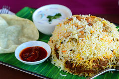 Kerala biryani thali served with curd and papad. Biryani served with pickle yogurt dip and fried papad Stock Photo