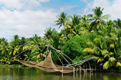 Kerala canal. Coco trees reflection and chinese fishing nets  at back waters of Kerala, India Royalty Free Stock Images