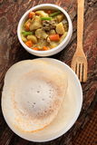 Kerala cuisine-Soft Appam served with hearty mutton stew. On a wooden background royalty free stock photo