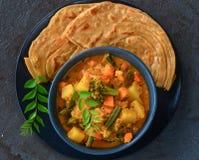 Indian Kerala meal-malabar parotha and stew. Kerala lunch South Indian thaali  sambhar,mixed veg curry and malabar parantha Royalty Free Stock Image