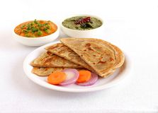 Kerala Paratha Indian Food with Salad. Kerala paratha, a type of Indian bread, with carrot and onion salad, and in the background are bowls of peas and carrot Royalty Free Stock Image