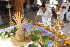 A kerala wedding flower decoration. 10 SEP 2010 GURUVAYUR KERALA INDIA - a priest lighting the kuthu vilakku on a kerala hindu malayalee wedding stage decoration Stock Images