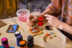 Keramiker för yrkesmässig kvinna som målar den keramiska souvenirmagneten i keramiker royaltyfria bilder