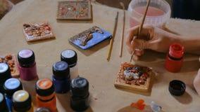 Keramiker f?r yrkesm?ssig kvinna som m?lar den keramiska souvenirmagneten i krukmakeriseminarium stock video