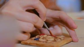 Keramiker f?r yrkesm?ssig kvinna som m?lar den keramiska souvenirmagneten i krukmakeriseminarium lager videofilmer