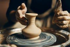 Keramiker som modellerar den keramiska krukan från lera på keramikers hjul arkivbilder