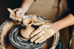 Keramiker som modellerar den keramiska krukan fr?n lera p? keramikers hjul royaltyfria bilder