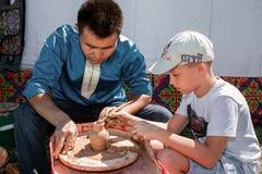 Keramikern gör krukor med en student royaltyfria foton