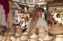 Keramikern säljer krukmakeri. Arkivbild