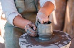 Keramikern skapar lergods på hjulet för keramiker` s royaltyfri fotografi