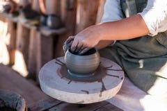 Keramikern skapar lergods på hjulet för keramiker` s arkivfoto