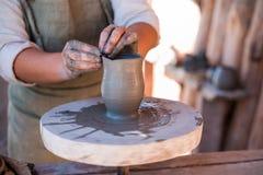 Keramikern skapar lergods på hjulet för keramiker` s arkivbilder