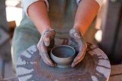 Keramikern skapar lergods på hjulet för keramiker` s royaltyfria bilder
