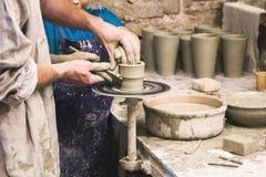 Keramikern undervisar för att hugga i lerakruka på det roterande krukmakerihjulet Royaltyfria Bilder