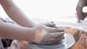 Keramikern undervisar hans hantverk till barnen Krukmakerigruppseminarium Lera som formar på keramikers hjul och att avfyra stock video