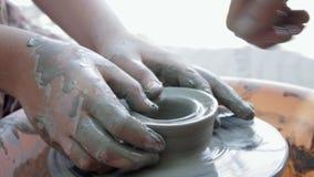 Keramikern undervisar hans hantverk till barnen Krukmakerigruppseminarium Lera som formar på keramikers hjul och att avfyra arkivfilmer