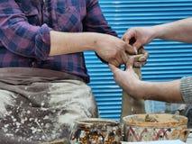 Keramikern undervisar hur man formar leran på hjulet arkivfoto