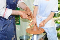Keramikern undervisar pojken att arbeta på keramikerhjulet royaltyfri foto