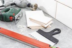 Keramikfliesen und Werkzeuge für Dachdecker, Flieseninstallation Heimwerken, Erneuerung - keramischer Fliesenbodenkleber lizenzfreie stockfotografie