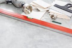 Keramikfliesen und Werkzeuge für Dachdecker, Flieseninstallation Heimwerken, Erneuerung - keramischer Fliesenbodenkleber stockfotos