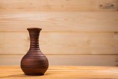 Keramische Flasche auf hölzernem Hintergrund lizenzfreie stockbilder