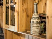 Keramische gestickte Weinflasche der Weinlese auf hölzernem Regal Stockbild