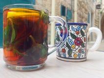 Keramische Kaffeetasse und türkische Tee-Glasschale auf Holztisch herein Stockbild