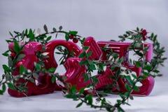 Keramische Liebesbriefe verzieren mit den Weihnachtslametta, die auf einem weißen Hintergrund angezeigt werden lizenzfreie stockfotografie