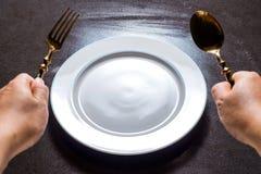 Keramische Platte auf dem Tisch mit dem Löffel und Gabel in der Hand, die f warten Lizenzfreie Stockfotos