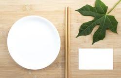 Keramische Platte mit Essstäbchen und Papierspott herauf weiße Karte auf wo Lizenzfreies Stockbild