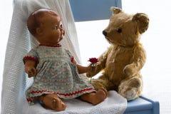 Keramische Puppe der Weinlese, antiker Teddybär und frische Rotrose stockfotografie