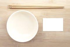 Keramische Schüssel mit Essstäbchen und Papierspott herauf weiße Karte flehen an an Stockfoto