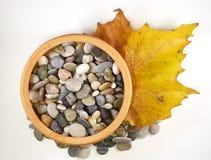 Keramische Schüssel mit Kieseln und Herbstblatt Lizenzfreies Stockfoto