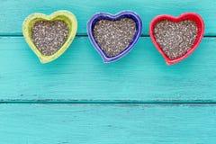 Keramische Schüsseln der Herzform mit Chia-Samen stockbilder