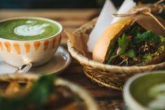 Keramische Schale mit grünem Tee nannte Matcha und ein Sandwich nahe Stockfotografie