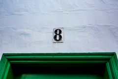 Keramische schwarze Weißwand der Nr. 8 über grüner Tür Lizenzfreies Stockbild