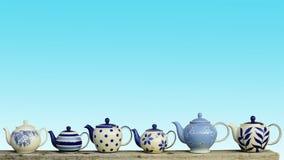 Keramische Teekanne mit blauem Pastellwandhintergrund Lizenzfreie Stockbilder