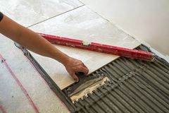 Keramische tegels en hulpmiddelen voor tegelzetter Arbeidershand die vloertegels installeren Het huisverbetering, vernieuwing - d stock afbeelding